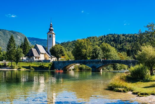 BOHINJ LAKE, SLOVENIA - AUGUST 24, 2016: Church of St. John the Baptist at Bohinj Lake is over 700 years old and is a beautiful example of Middle Age architecture and fresco painting in Slovenia.