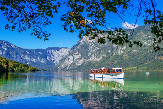 Tourists sightseeing Bohinj lake and surrounding from boat