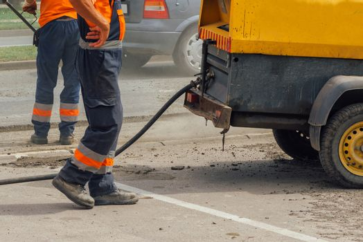 Unidentifiable road maintenance workers repairing driveway