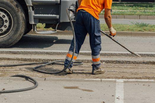 Unidentifiable road maintenance worker repairing driveway
