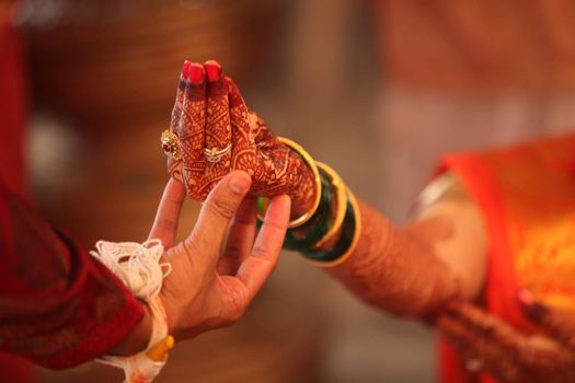An Indian groom holding the bride's hand during a traditional hindu wedding ritual