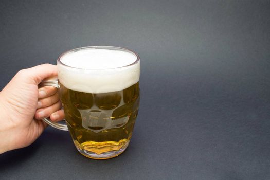 Hand holds golden pint of beer in a dark background