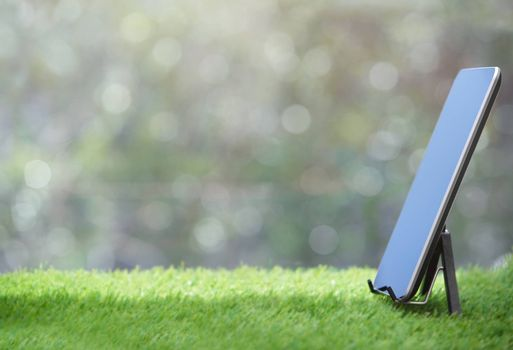 Tablet computer standing on a grass