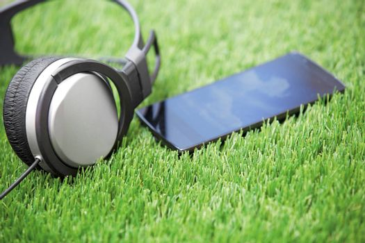 Headphones and smartphone laying on a grass