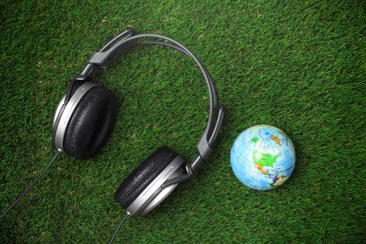 Headphone and earth globe on a grass