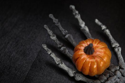 Skeleton hand holding Halloween pumpkin