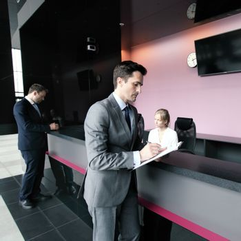Business people filling forms at front desk