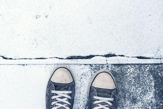 Pair of worn sneakers on concrete floor
