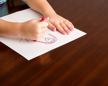 Image of a childs hands, a crayon, and paper on a table while she is creating her masterpiece