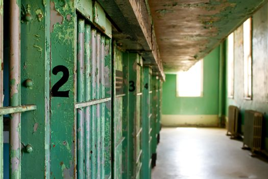 Shallow depth of field on a historic prison old worn down jail cells. focus on number 2.