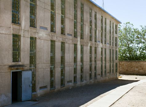 Prison building. can see windows with bars and an open door leading into the building