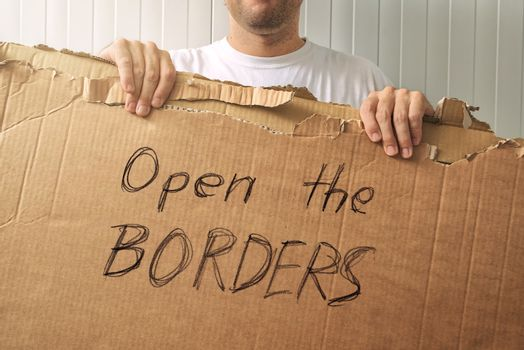 Refugee holding cardboard with Open the borders request