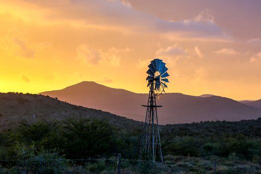 Water Pump Windmill on Arid Farmland at Sunset