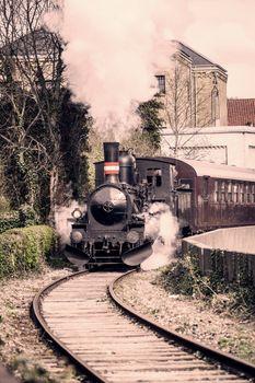 Steamy veteran train driving on a railway