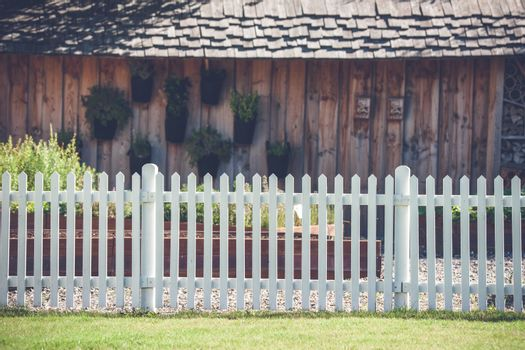 White picket fence in front af a wooden shed