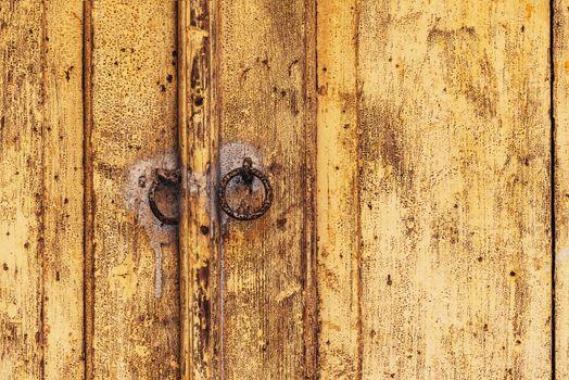 Weathered wooden door with rusty metal knockers