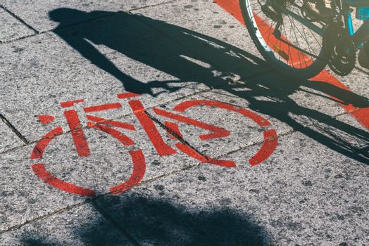 Shadow of female biker and bicycle route road marking