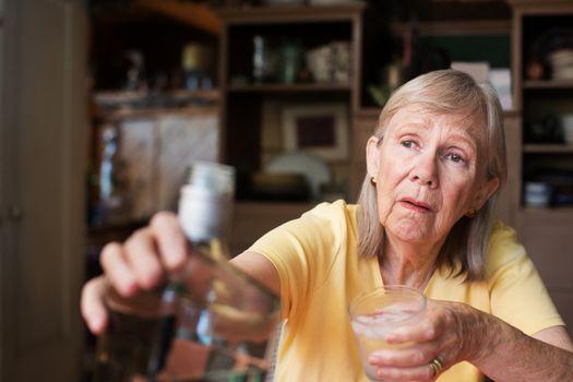 Woman reaching for bottle of liquor