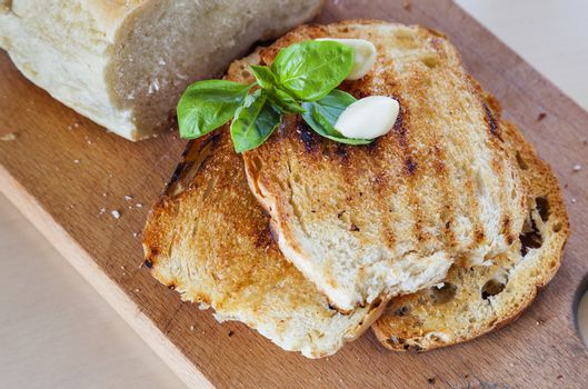 Three roasted slices of bread with garlic, fresh basil and a bread on the side.