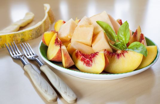 Plate with sliced fruits - peaches and melon with fresh basil and two forks