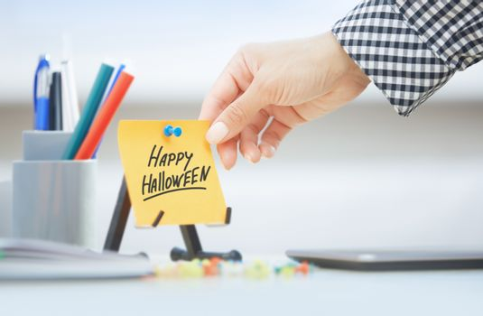 Hand taking sticky note with Happy Halloween text