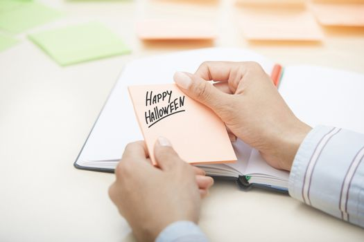Hands holding sticky note with Happy Halloween text