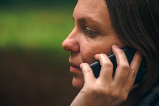 Woman with serious face expression talking on phone in park