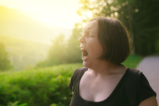 Young adult woman yawning outdoors in the morning