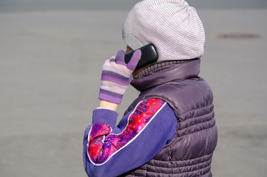 a Little girl speaks by mobile phone while standing outdoors.