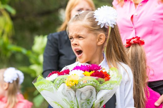 First grader with a bouquet of flowers yawns at school in a crowd