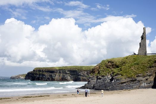 tourists walking the beach cliffs and castle on ballybunion beach county kerry ireland