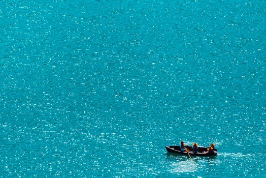 Unrecognizable people rowing in boat on lake, vast water surface as copy space