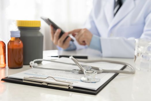 stethoscope and document on desk's doctor by doctor working in background