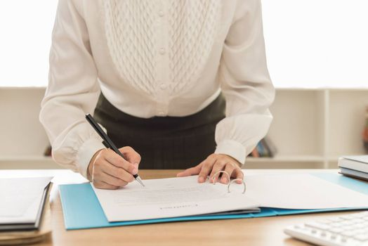 woman working in her office with documents on desk.
