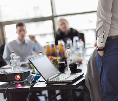 Business man making a presentation at office. Business executive delivering a presentation to his colleagues during meeting or in-house business training. Rear view. Business and entrepreneurship.