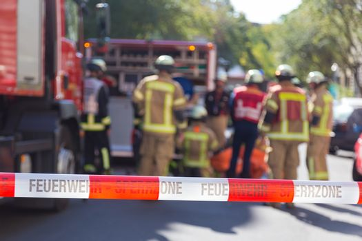 Team of firefighters by firetruck on accident location.