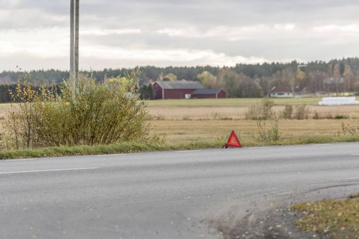 Warning Triangle on Road with field in the background.