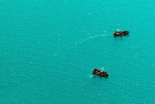 People rowing in boats on lake, enjoying summer