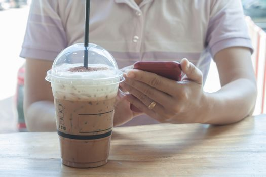 Woman hand holding phone with background of iced coffee, stock photo
