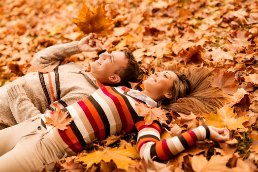 Beautiful smiling couple enjoying in sunny forest in autumn colors. They are lying on the falls leaves.