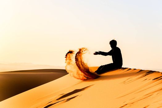 Silhouette of young man playing with sand on top of a dune of sahara