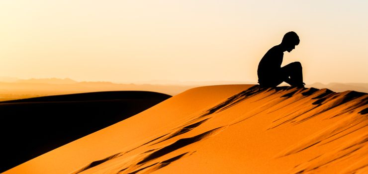 Panoramic view of silhouette of meditating young man sitting on top of a dune of sahara