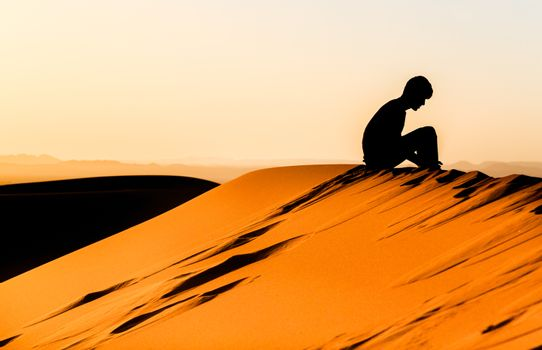 Silhouette of meditating young man sitting on top of a dune of sahara