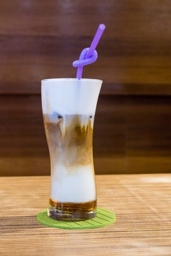 Cold capuccino in glass with straw