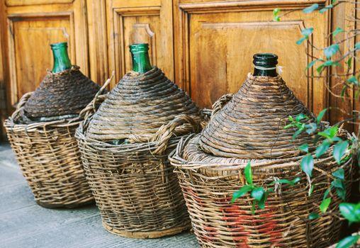 Vintage empty wicker wine bottles in Tuscany, Italy