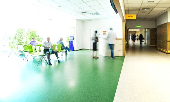 View of the registration desk, waiting area and a corridor in modern hospital with blurred figures of patients and a copy space.