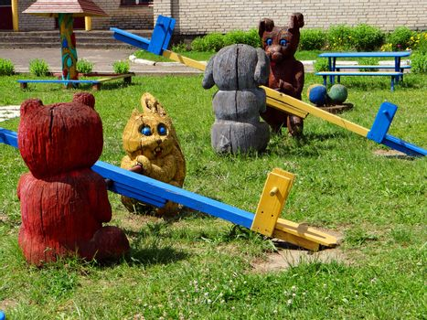 Children's playground with wooden swings and funny animals