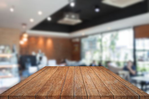 Perspective top brown wooden with blurred cafe interior for background. product display template