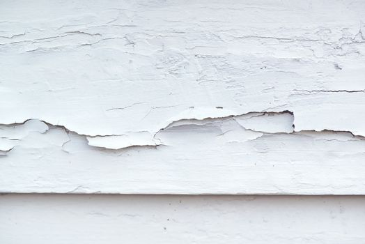 Cracked white paint on plank surface, abstract wooden background