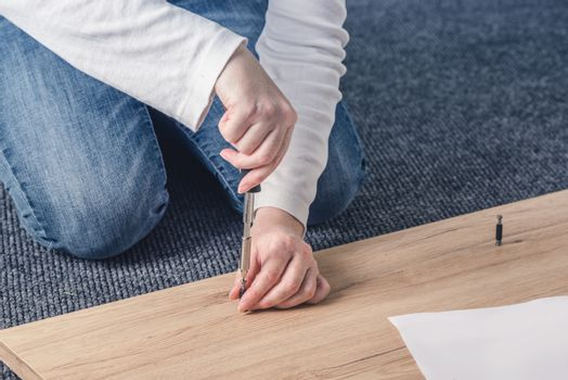 Woan assembling furniture at home, hand with screwdriver